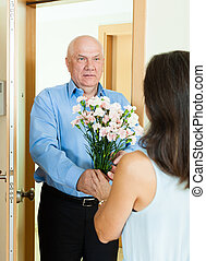 Mature man giving bunch of flowers to woman at home door