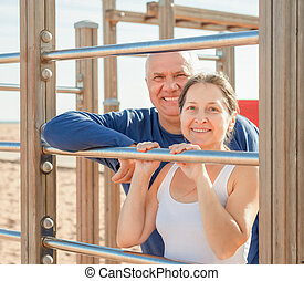 Mature couple together training on pull-up bar - Sporty...