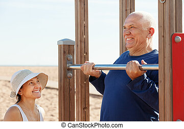 mature couple training with chin-up bar - healthy mature...
