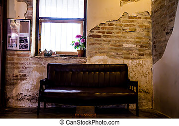Black sofa in the old brick walls