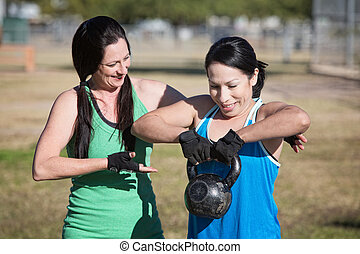 Woman Assisting Student with Weights - Friendly fitness...