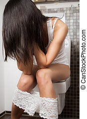 Young woman using the toilet sitting on the bowl with her...