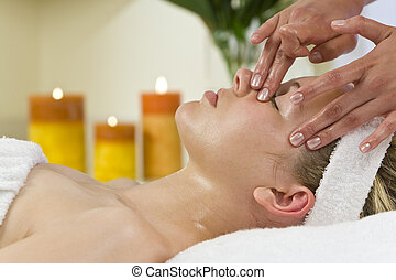 Facial Treatment - A young woman relaxing at a health spa...