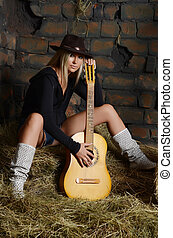 The woman with guitar on hay - The woman with a guitar on...