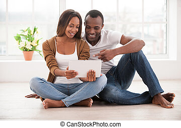 Working at their new tablet. Beautiful young African couple...