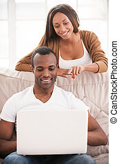 Surfing the net together. Handsome young African man sitting...