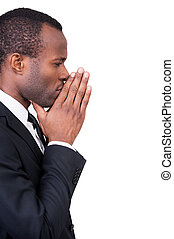 Thinking about new solutions. Side view of thoughtful young African man in formalwear touching his chin with clasped hands while standing isolated on white background