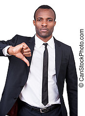 I said no! Serious young African man in formalwear showing his thumb down and looking at camera while standing isolated on white background