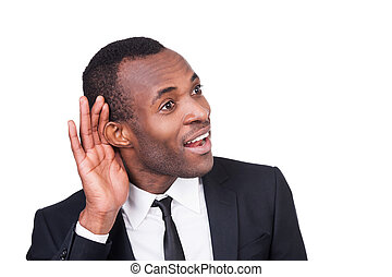 What did you say? Cheerful young African man in formalwear holding hand near ear and smiling while standing isolated on white background