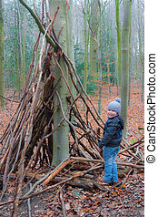 Little kid building a tipi on a winter day