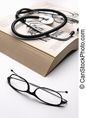 Glasses, phonendoscope and medicine textbook - Reading...