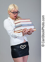 Beautiful student is holding a lot of books