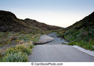 end of the road - Road ends abruptly into a dry water stream