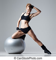 Fitness with gym ball - Athletic woman stands on a gym ball...
