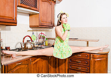 Beautiful pinup woman doing splits in kitchen