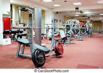 Interior of a gym - Bench press and various equipment in a...