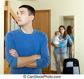 wife with baby girl and suitcase leaving from home
