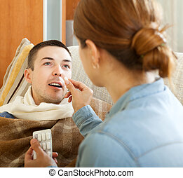 Wife giving pills to husband