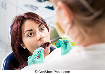 Dental inspection - Dentist checking dental hygiene on...