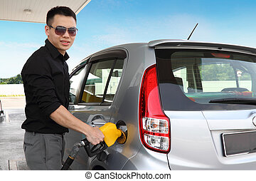 Man refuelling a car - A young man refueling his car