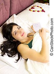 Beautiful woman in bed with love letter from boyfriend