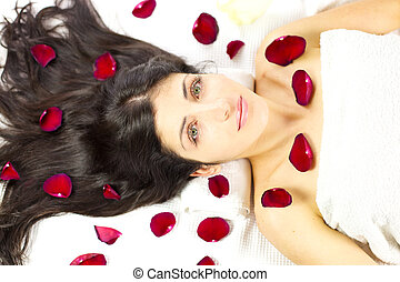 Gorgeous woman laying surrounded by rose petals