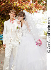 Young and beautiful bride and groom smilling