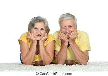 Cute old couple drinking tea - Cute old couple is lying at...