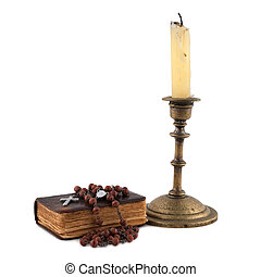 the bible with beads and candles isolated on white...