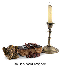 the bible with beads, an angel and candles isolated on white...