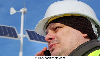 Electrical Engineer with cell phone near solar panels
