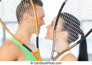 Fitness couple. Loving couple kissing behind tennis racket