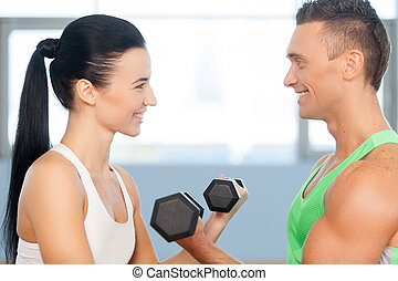 Couple having fun lifting weights. Athletic man and woman with a dumbbells