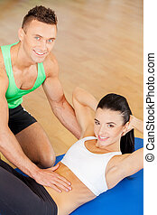 Training instructor. Woman training at the gym with a personal trainer