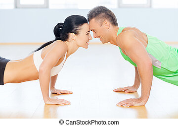Fit couple. Man and woman doing push-up looking to each...
