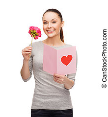 smiling woman with postcard and flower - love, holidays and...