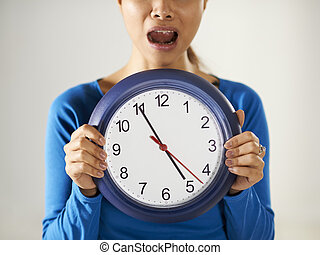 asian girl holding big blue clock with stress - portrait of...
