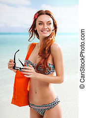 Redhair woman on beach - Redhear woman with sunglasses...