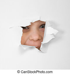 Eye looking through hole in sheet of paper - Child\'s eye...