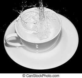 water in the cup with splashes on a black background