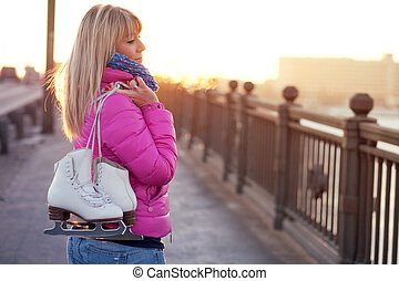 Beautiful young blond woman walking on bridge with skates in...
