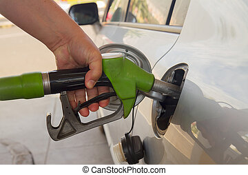 refilling car with fuel - close up of hand with pump...