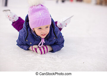 Adorable little girl sitting on ice with skates after the...