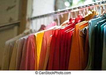 Clothes on a Rail - A row of brightly coloured shirts and...