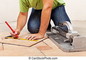 Worker hands laying ceramic floor tiles - measuring and...