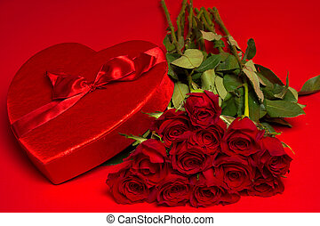 Roses and a red heart box on a red background - a dozen long...