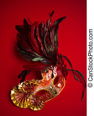 A red, gold and black mardi gras mask on a red background -...