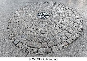Manhole with drainage sewerage in cobblestone circle