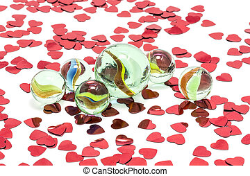 Toy marbles on white background, surrounded by so many red...