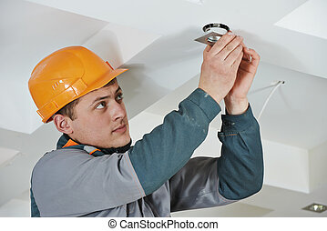 Electrician at spot light installation - electrician worker...